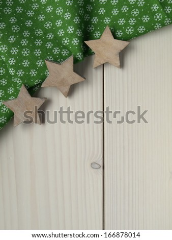 wooden background with fabric, stars and snowflakes - stock photo