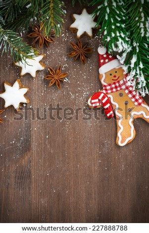 wooden background with fir branches, cookies and gingerbread man, vertical, top view, close-up - stock photo