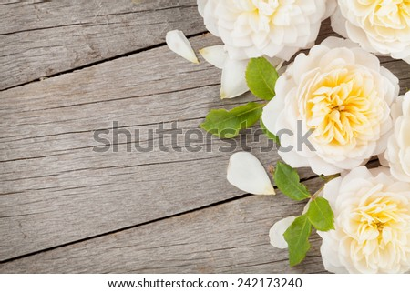 Wooden background with fresh rose flowers and copy space - stock photo