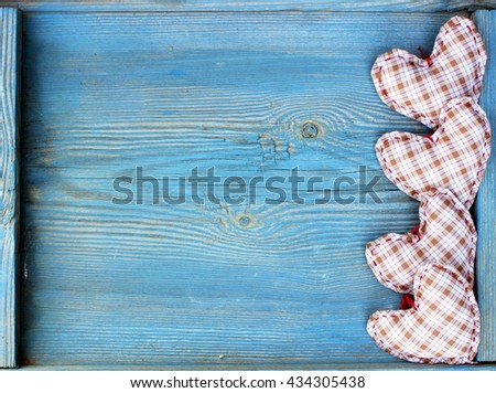 Wooden background with handmade textile hearts on old wooden plank. Blue color. Rustic design - stock photo
