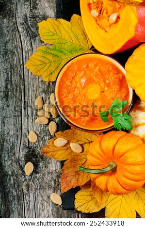 Wooden background with pumpkins and soup. Copy space - stock photo