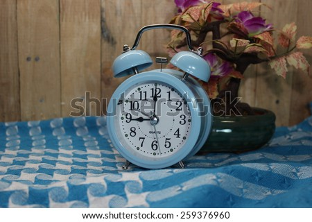 Wooden background with retro alarm clock on cloth