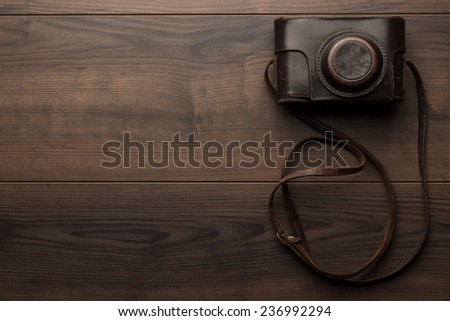 wooden background with retro still camera in case