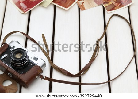 wooden background with the camera and old photos/retro camera and photos