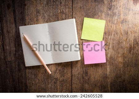 Wooden background with two blank colorful sticky notes and notebook and pencil - stock photo