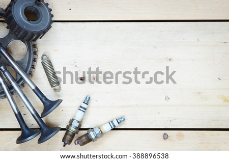 Wooden background with various spare parts for automobile - stock photo