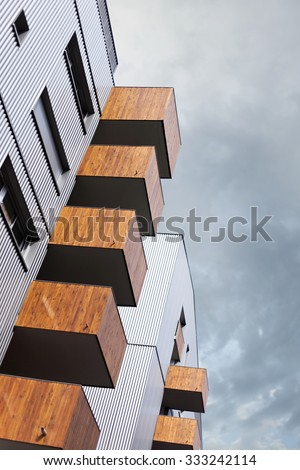 Wooden balconies on the facade of a modern building - stock photo