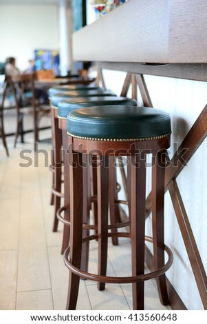 Wooden bar stools in a restaurant at day - stock photo