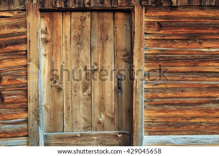 Wooden barn door and wall on a log cabin, Wyoming, USA. - stock photo