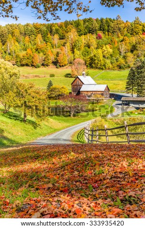 Wooden barn in fall foliage landscape in Vermont countryside. - stock photo