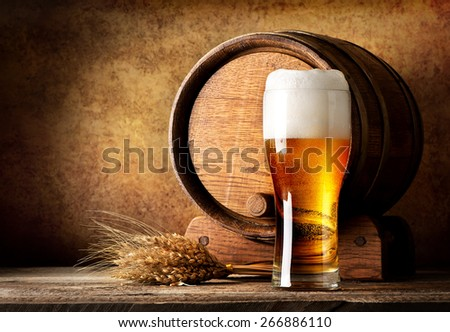 Wooden barrel and beer with wheat on a wooden table - stock photo