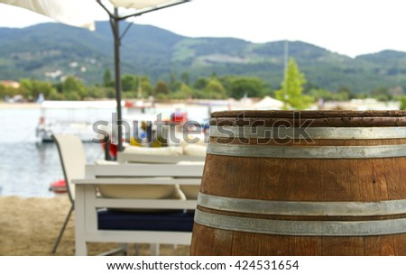 Wooden barrel in the beach cafe, boat on the seashore and cafe, fishing boat on the pier, view from the cafe with barrel on the boat on the seashore, table in the cafe on the sea - stock photo