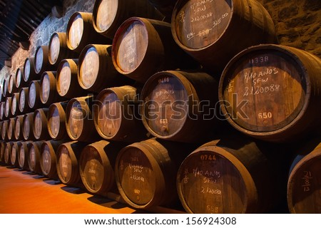 wooden barrels hold Port fortified wine to mature in wine cellars , Portugal - stock photo