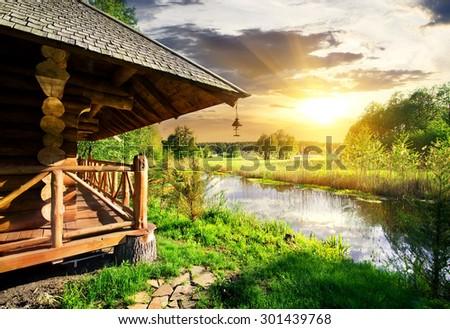 Wooden bathhouse near lake at the sunset - stock photo