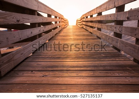 wooden beach boardwalk path at sunset leading towards light