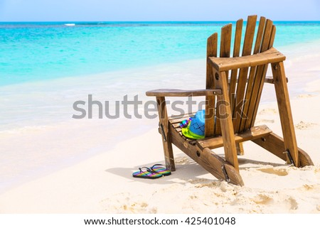 Wooden beach chair with hat and slippers at beach cost, summer holiday concept   - stock photo