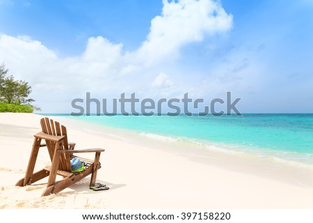 Wooden beach chair with hat and slippers at tropical beach, summer holiday concept