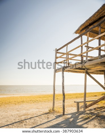 Wooden beach hut with thatched roof looks out over the Makgadikgadi Pan in Botswana, Africa - stock photo