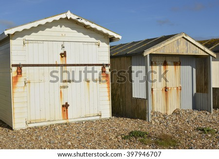 Wooden beach huts on shingle beach at Lancing, Near Brighton, West Sussex, England
