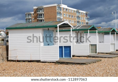 Wooden beach huts on the shingle beach at Bexhill-on-Sea in East Sussex, England.