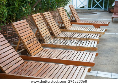 Wooden bed beside the pool. The beds are arranged behind the pool's edge. - stock photo