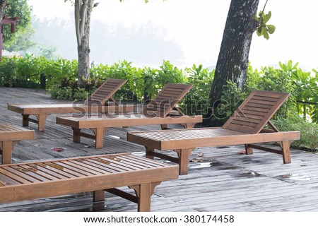 Wooden bed on the balcony. Beds made of wood under a tree on the terrace. - stock photo