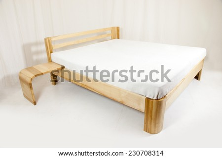 wooden bed - piece of furniture in front of white background - stock photo