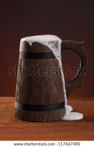 Wooden beer mug with foam on a dark red background. - stock photo