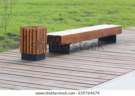 Wooden Bench And Trash Can In The Park