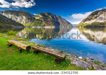 Wooden bench at mountain lake in the Alps - stock photo