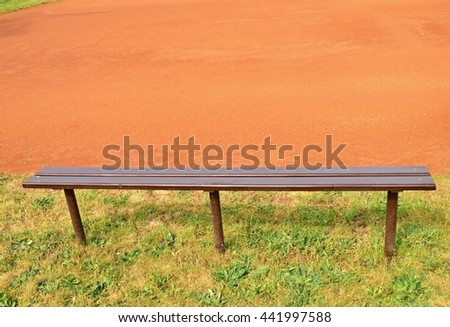 Wooden bench, empty seats on outdoor tennis court. Stadium bench with worn paint on rusty metal poles. Red milled brick surface on playground - stock photo