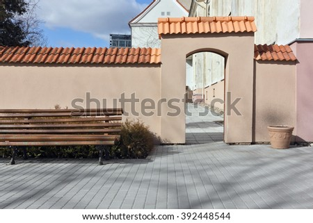 Wooden bench for rest and smoking on the quiet small street of the old European city.Sunny spring day urban landscape - stock photo