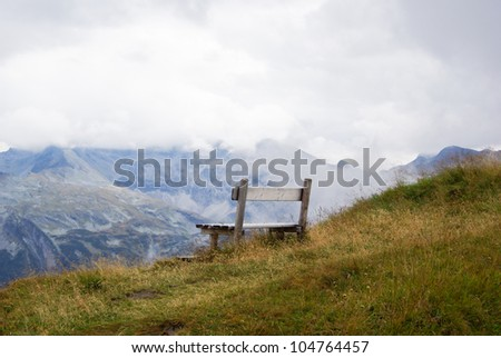 Wooden bench for resting in a mountainous landscape a cloudy day in Austria.