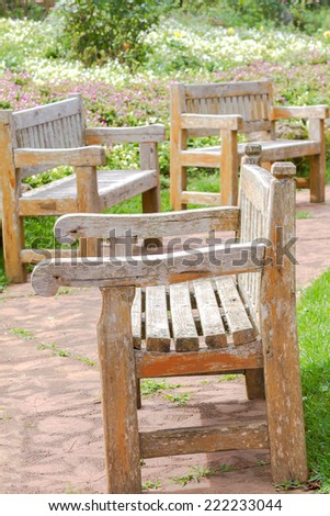 Wooden Bench in a wildflower garden. - stock photo