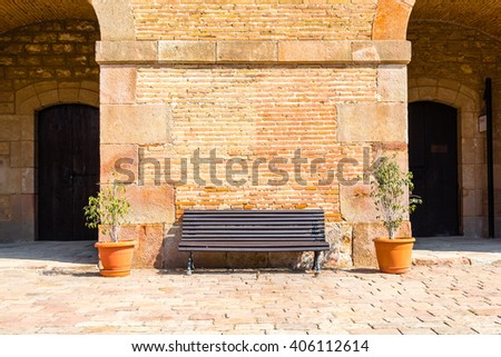 wooden bench in front of a brick wall