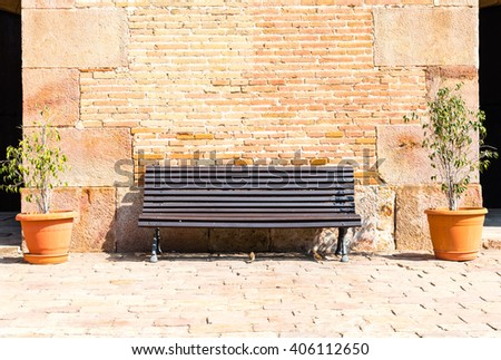 wooden bench in front of a brick wall  - stock photo