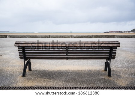 Wooden bench in front of an urban beach - stock photo