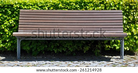 wooden bench in front of bush - stock photo
