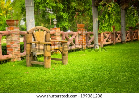 Wooden bench in garden - stock photo