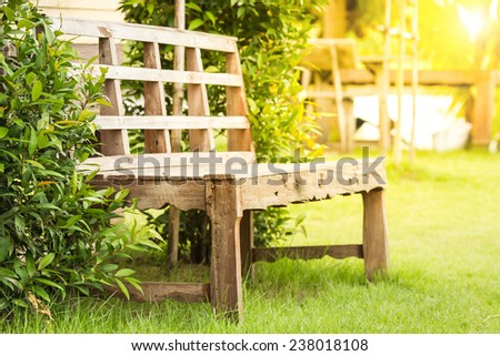 Wooden bench in garden. - stock photo