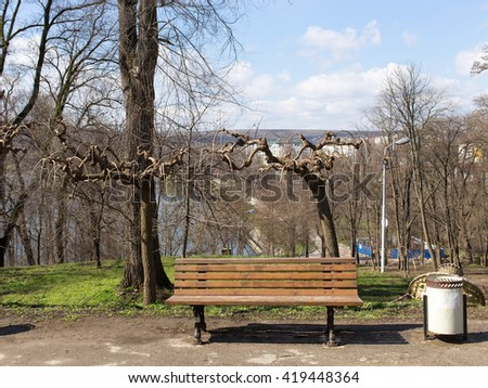 Wooden bench in the park with lake on the background. - stock photo