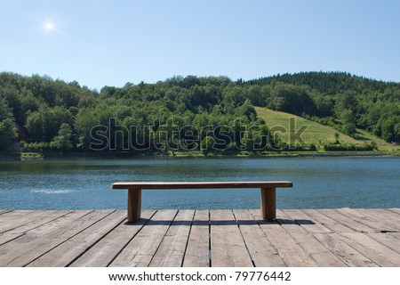 wooden bench looking at the lake and forest - stock photo