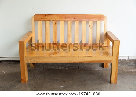 Wooden bench near the white wall behind the house. - stock photo