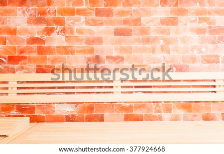 Wooden bench on hymalayan salt wall decoration in sauna room - stock photo