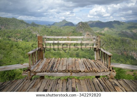 Wooden bench over tropical forest - stock photo