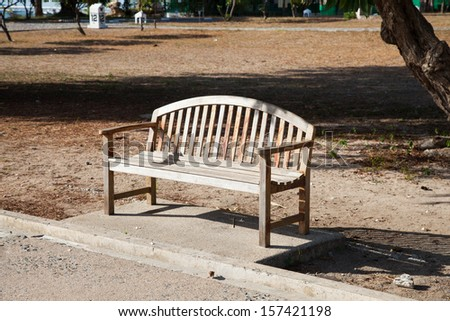 Wooden bench under a tree near the pathway in the park. - stock photo