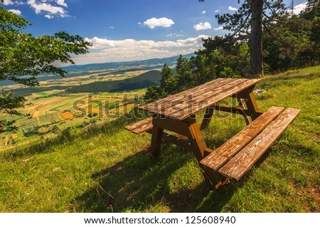 Wooden bench without people outdoors - stock photo