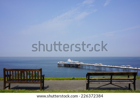 Wooden Benches and Llandudno Pier in Background - stock photo