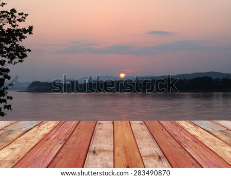 Wooden beside lake with sunset - stock photo