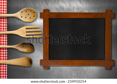 Wooden Blackboard and Kitchen Utensils / Rustic and empty blackboard, four wooden kitchen utensils, fork, spoons and ladles on brushed metallic background with red and white checkered tablecloth - stock photo